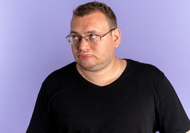 Übergewichtiger mann in der brille, die schwarzes t-shirt trägt, das mit traurigem ausdruck über blauer wand beiseite schaut