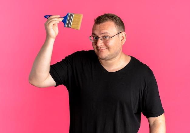 Übergewichtiger mann in der brille, die schwarzes t-shirt trägt, das pinsel mit lächeln auf gesicht über rosa zeigt
