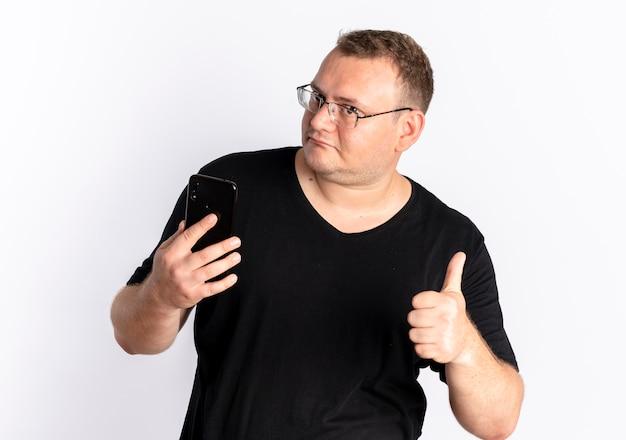 Übergewichtiger mann in der brille, die schwarzes t-shirt trägt, das seinen smartphone-bildschirm betrachtet, der daumen oben zeigt, die über weißer wand stehen