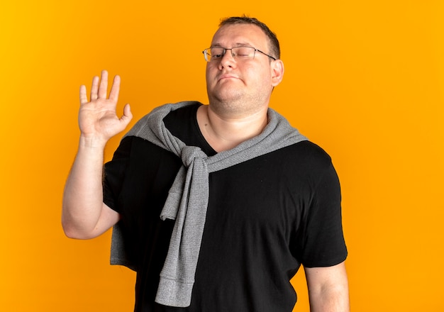 Übergewichtiger mann in der brille, die schwarzes t-shirt trägt, das sicher winkend mit hand steht, die über orange wand steht