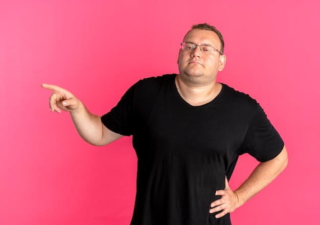 Übergewichtiger mann in der brille, die schwarzes t-shirt trägt, das sicher zeigt, mit zeigefinger zur seite stehend über rosa wand zeigt