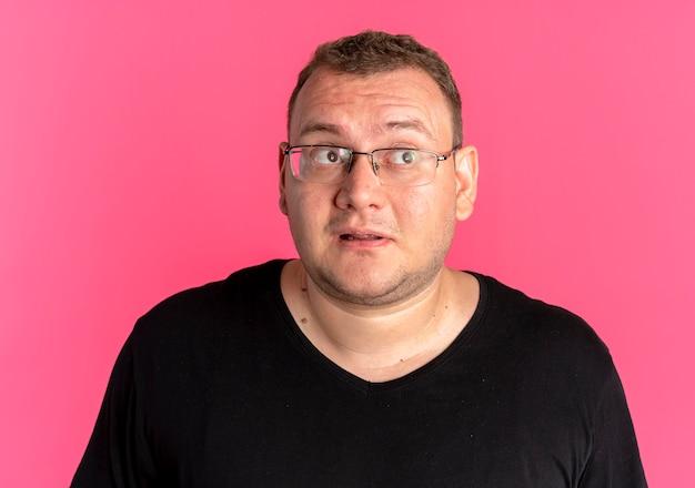 Übergewichtiger mann in der brille, die schwarzes t-shirt trägt, das überrascht und glücklich über rosa schaut