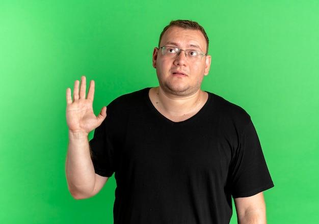 Übergewichtiger mann in der brille, die schwarzes t-shirt trägt, das verwirrt schaut und mit hand über grün winkt