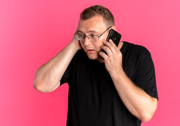 Übergewichtiger mann in der brille, die schwarzes t-shirt trägt, das verwirrt spricht, während auf mobiltelefon steht, das über rosa wand steht