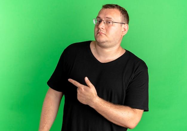 Übergewichtiger mann in der brille, die schwarzes t-shirt trägt, das verwirrtes pointign mit zeigefinger zur seite über grün sieht