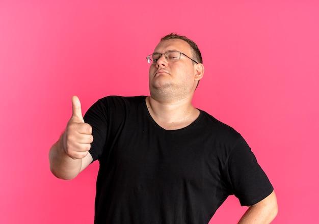 Übergewichtiger mann in der brille, die schwarzes t-shirt trägt, das zuversichtlich schaut, daumen über rosa zeigend