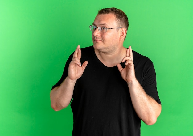 Übergewichtiger mann in der brille, die schwarzes t-shirt trägt und wünschenswerten wunsch macht, finger mit glücklichem gesicht über grün zu kreuzen