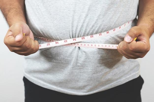 Übergewichtiger mann möchte trainieren und gewicht kontrollieren.