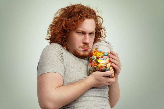 Übergewichtiger molliger europäischer mann mit dem gelockten ingwerhaar, das glas der süßigkeiten fest hält