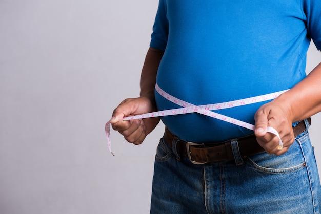 Übergewichtiger oder fetter erwachsener mann in sehr engen jeans mit maßband