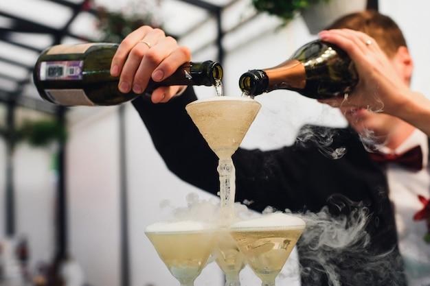 Übergibt braut und bräutigam mit den champagnerflaschen, die wein in gläser gießen