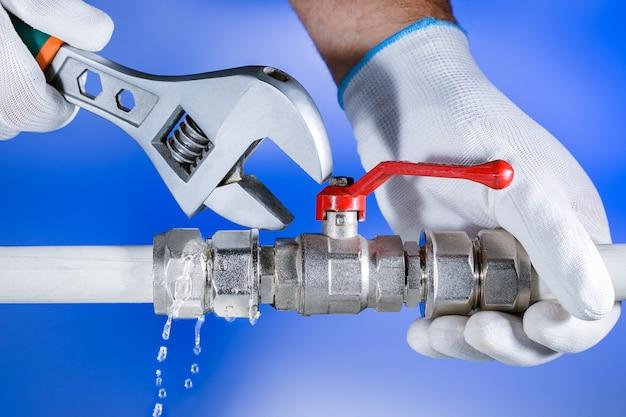 Übergibt klempner bei der arbeit in einem badezimmer und plombiert reparaturservice. wasserleck. sanitär reparieren.