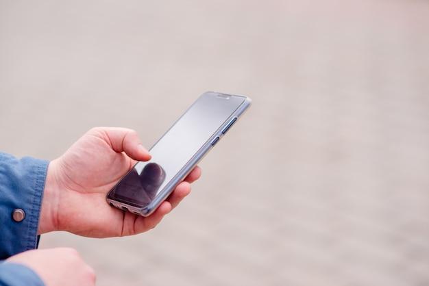 Übergibt telefon des jungen mannes für das suchen, auf internet erziehend. online-bank, horizontale ansicht der internet-sicherheit