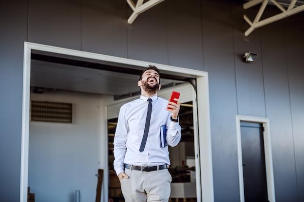 Überglücklich bärtiger kaukasischer ceo in hemd und krawatte, der vor druckerei steht und smartphone benutzt.