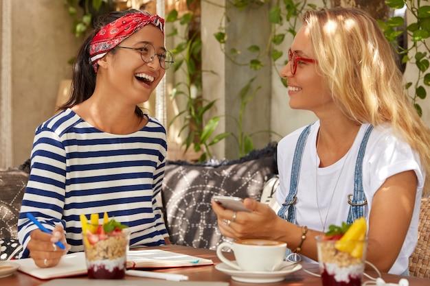 Überglücklich lachen zwei frauen glücklich, während sie meinungen über das planungsprojekt austauschen, während der kaffeepause kommunizieren, aufzeichnungen im veranstalter schreiben, köstliche nachspeisen essen, freizeitkleidung und brillen tragen