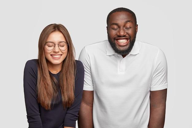 Überglücklich lächelnder dunkelhäutiger kerl und seine freundin lachen positiv über lustigen witz