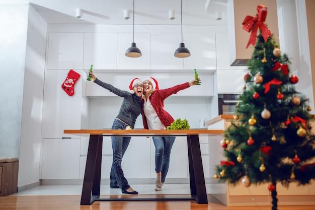 Überglückliche ältere frau, die sich am silvesterabend mit ihrer tochter umarmt. beide haben weihnachtsmützen auf den köpfen und bier.