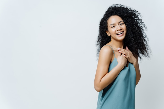 Überglückliche afroamerikanische frau lacht positiv, hält die hände auf der brust, hört lustige witze, drückt glück aus
