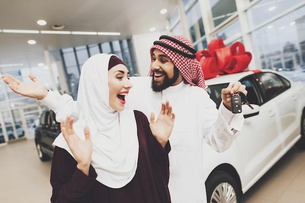 Überglückliche arabische frau erhielt autoschlüssel, die mann geschenk kauft.