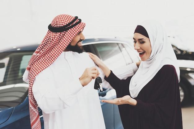 Überglückliche arabische frau erhielt autoschlüssel vom liebevollen mann.