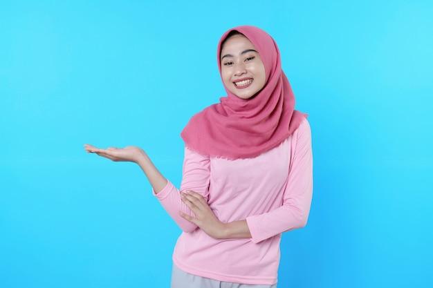 Überglückliche attraktive frau zeigt etwas auf ihrer hand, überraschende geste mit rosa t-shirt