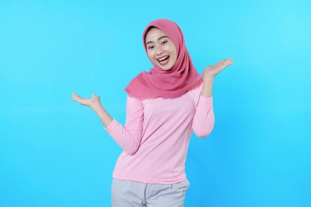 Überglückliche attraktive frau zeigt größe etwas großes, überraschende geste mit rosa t-shirt