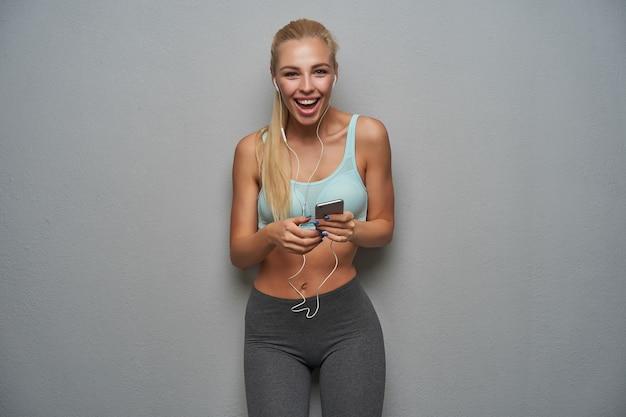 Überglückliche attraktive junge schlanke blonde frau mit pferdeschwanzfrisur, die musik mit kopfhörern und smartphone hört, während über grauem hintergrund in sportlichen kleidern posiert