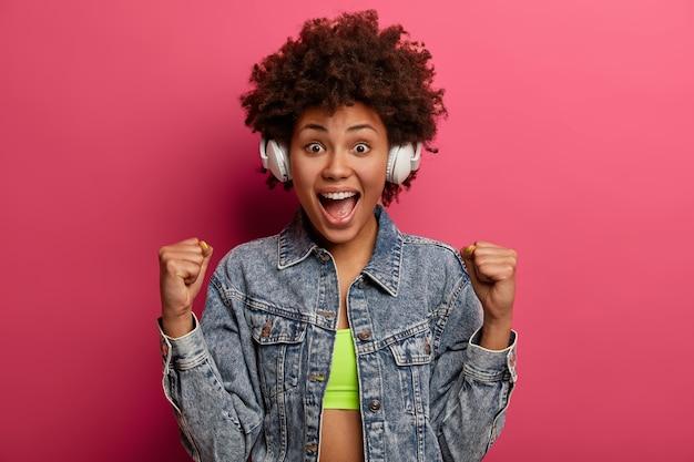 Überglückliche emotionale frau hebt geballte fäuste, fühlt sich optimistisch, ruft laut aus