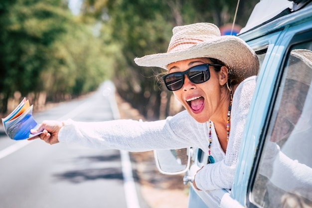Überglückliche erwachsene hübsche frau vor dem fenster ihres oldtimers mit einer guida-karte zur hand, die um hilfe bittet oder spaß hat