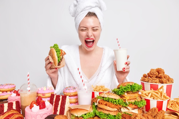 Überglückliche frau isst einen hamburger und einen milchshake
