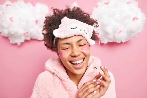 Überglückliche frau lacht glücklich lächelt breit schließt die augen wach in guter laune trägt schlafmaske warmer pyjama schließt die augen vor zufriedenheit wendet schönheitspads an, um falten unter den augen zu reduzieren