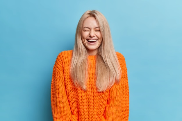 Überglückliche frau mit blonden langen haaren lacht positiv hört etwas lustiges schließt die augen zeigt weiße zähne trägt orange gestrickten pullover