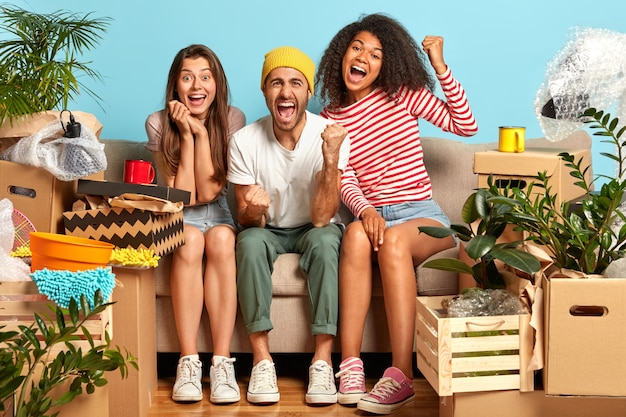 Überglückliche freunde sitzen auf der couch, umgeben von kisten