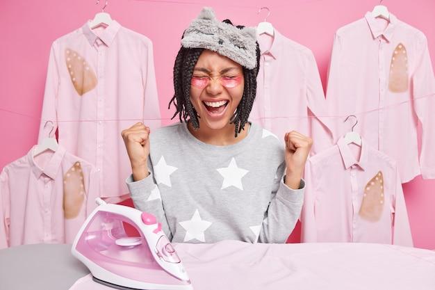 Überglückliche gemischtrassige hausfrau posiert in der nähe des bügelbretts, um kleidung zu bügeln, ballt vor freude die fäuste im schlafanzug und trägt schönheitsflecken unter den augen auf