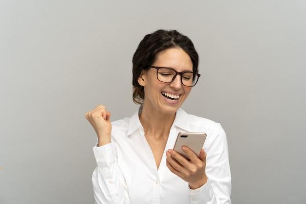 Überglückliche geschäftsfrau, die nachricht auf smartphone liest, ja-geste zeigt, gute nachrichten genießt