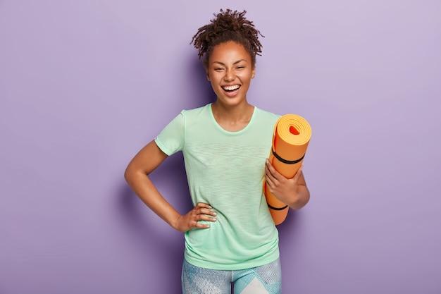 Überglückliche gesunde dunkelhäutige sportlerin hält die hand auf der hüfte, hält die aufgerollte fitnessmatte, ist in guter körperlicher verfassung, trainiert jeden tag sport, trägt t-shirt und leggings. menschen, yoga