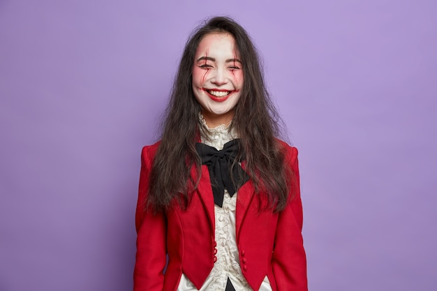 Überglückliche glückliche frau geist feiert halloween trägt schreckliches make-up in karneval kostüm posiert gegen lila wand gekleidet