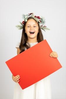 Überglückliche glückliche mädchen in einem weihnachtskranz, die ein rotes leeres papier mit kopienraum isoliert auf einem ...