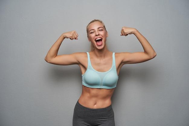 Überglückliche hübsche blonde dame in guter körperlicher form posiert über hellgrauem hintergrund in minzoberteil und grauen leggins und schaut freudig zur kamera mit weit geöffnetem mund und erhobenen händen