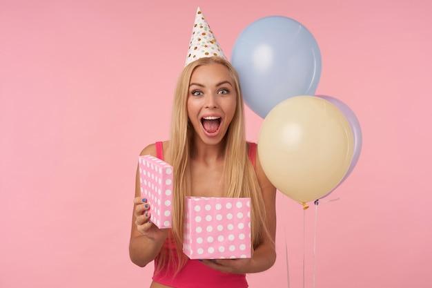 Überglückliche hübsche junge blonde frauendame mit lässiger frisur, die glückliche reaktion auf das erhalten eines fantastischen geschenks zeigt, das über rosa hintergrund im geburtstagshut aufwirft und kamera mit breitem fröhlichem lächeln betrachtet