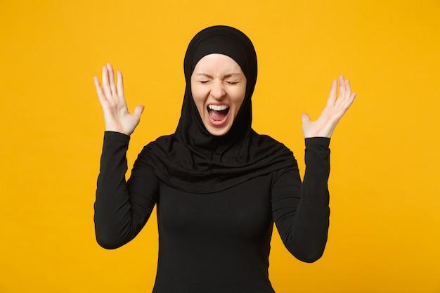 Überglückliche junge arabische muslimische frau in hijab-schwarzer kleidung, die gewinnergeste macht, sagen ja isoliert auf gelber wand, porträt menschen religiöses lifestyle-konzept.