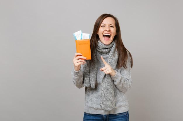 Überglückliche junge frau in grauem pullover, schal zeigt zeigefinger auf pass-bordkarte einzeln auf grauem hintergrund. gesunde mode-lifestyle-leute aufrichtige emotionen, konzept der kalten jahreszeit.
