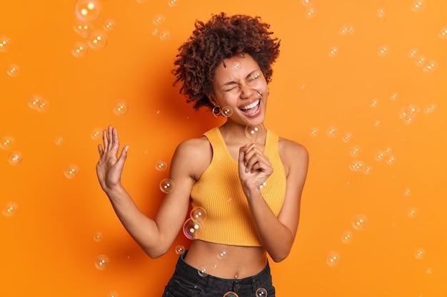 Überglückliche junge frau mit lockigen haaren singt lied hält hand, als ob mikrofon handfläche hebt