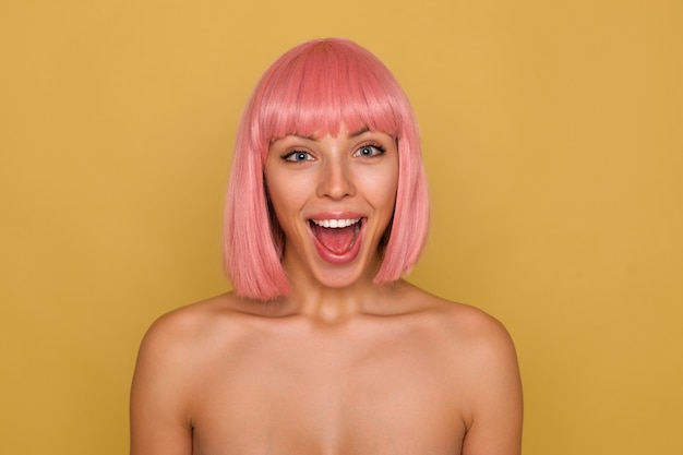 Überglückliche junge schöne pinkhaarige frau mit bob-frisur, die glücklich in die kamera mit weit geöffnetem mund schaut und in hochstimmung ist, während sie über senfwand steht