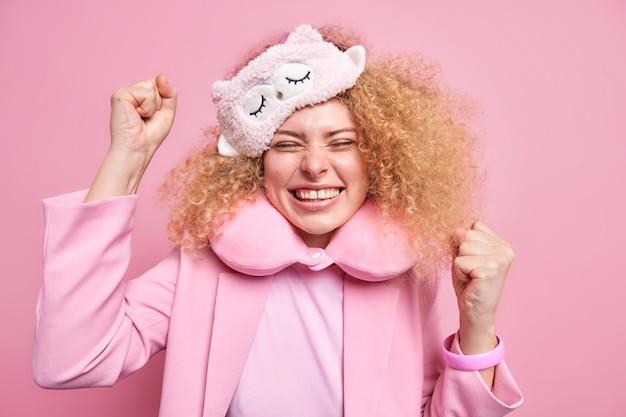 Überglückliche, lockige europäische frau ballt fäuste mit triumph feiert positive nachrichten lächelt breit trägt schlafmaske aufgeblasenes nackenkissen isoliert über rosa wand. frohes erwachen.