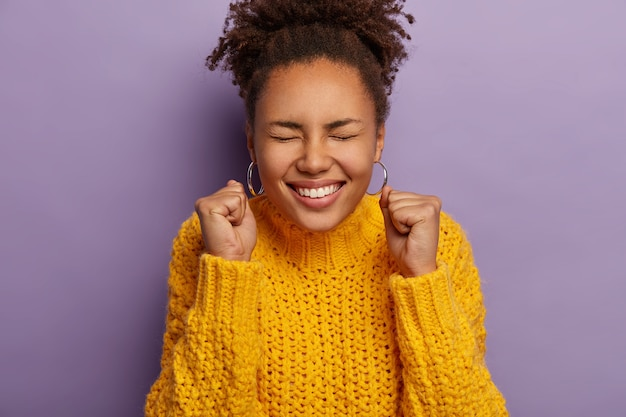 Überglückliche lockige frau hebt geballte fäuste, ist aufgeregt, feiert erfolg, trägt einen warmen gelben strickpullover
