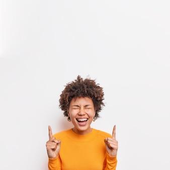 Überglückliche, lockige junge frau lacht glücklich punkte oben zeigt glücklich etwas lustiges gekleidet in einem lässigen orangefarbenen pullover isoliert über weißer wand. werbekonzept.