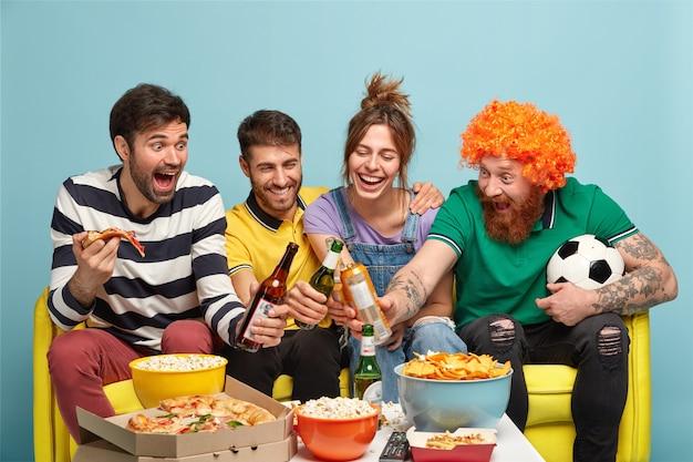 Überglückliche mitbewohner in der wohnung feiern den sieg des lieblingsteams, klirren flaschen mit bier