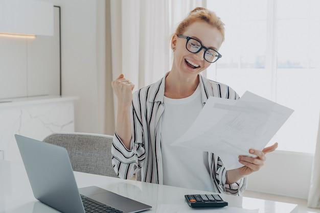 Überglückliche rothaarige frau ruft ja aus und feiert geldrückerstattung oder letzte letzte hypothekenzahlung