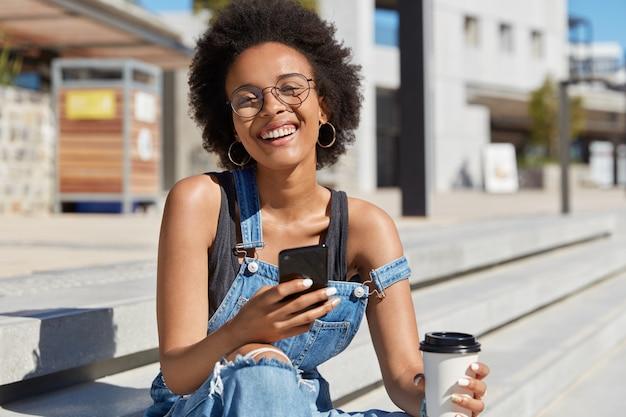Überglückliche schwarze dame lacht mit lustigem ausdruck, liest anekdote in sozialen netzwerken auf dem smartphone, trinkt kaffee zum mitnehmen, gekleidet in stilvolles outfit. mixed race frau wartet auf internationalen anruf